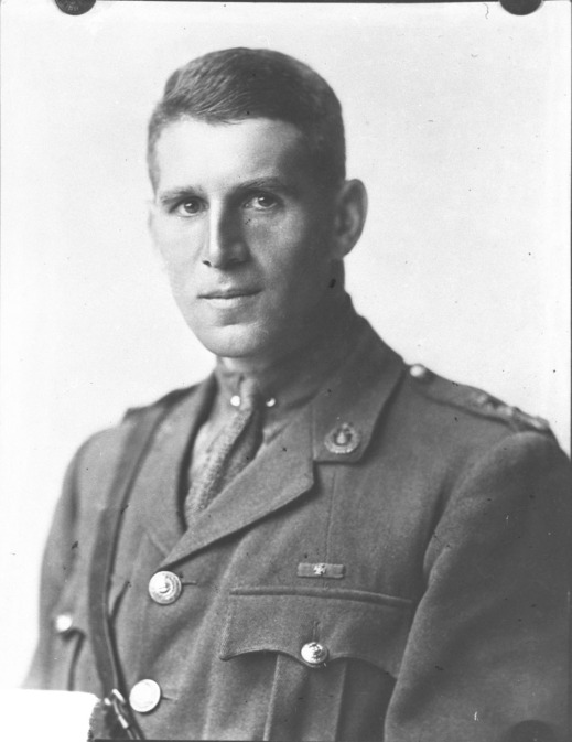 A black-and-white portrait of an officer wearing a Sam Brown belt and looking directly at the viewer.