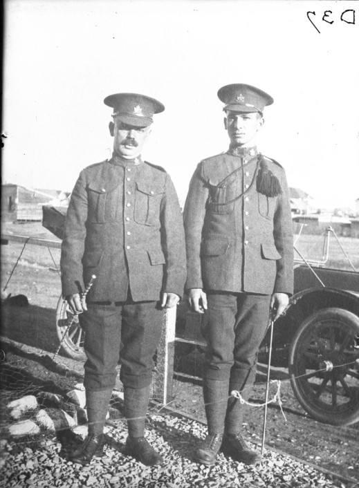 A black-and-white photograph of two soldiers standing side by side in front of an automobile.