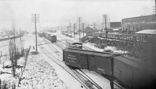 A black and white photograph of a partially derailed train in a train yard. Snow covers the ground and a city can be seen in the background.