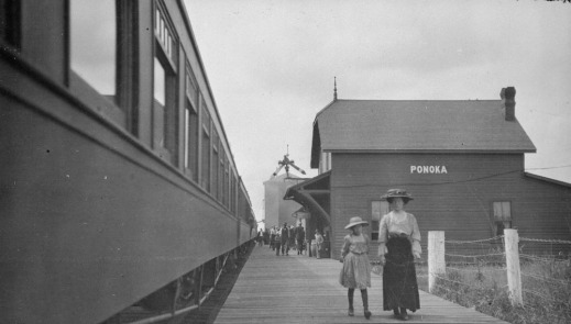 A black-and-white photograph showing a woman and child walking down a wooden platform along a train.