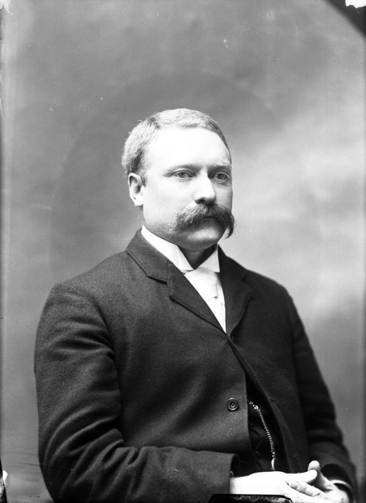 Black-and-white photo of a man with a moustache, wearing a suit and a white shirt.
