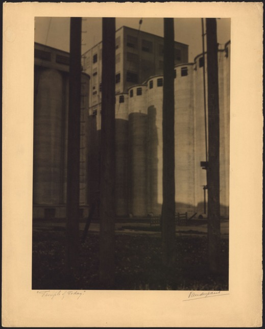 Black-and-white photo of a grain elevator with tall, circular towers in front of a taller rectangular building.
