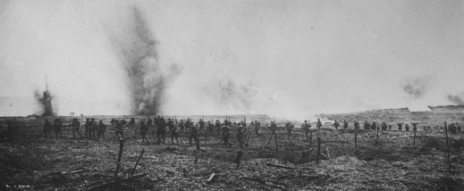 A black-and-white photo of soldiers advancing across a field, with shells exploding just in front of the advancing column.