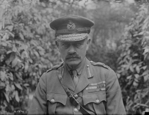 A black-and-white photo of a uniformed man with a moustache, wearing an officer's cap and a Sam Browne belt. His tunic is festooned with medals and military decorations, and he is staring directly and impassively into the camera.