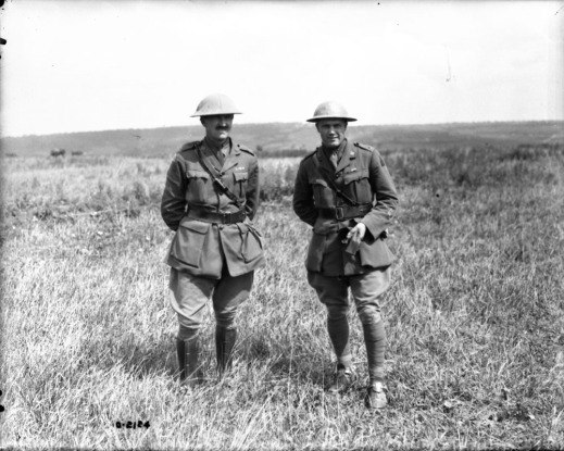 A black-and-white photograph of two men in uniform standing in a field.