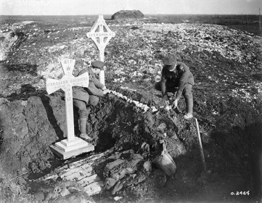 "A black-and-white photograph of two men adorning a makeshift grave with white stones in a desolate landscape that has patches of snow and frost on the ground. The grave is marked by a cross with the words ""L.S. [Lance-Sergeant] E.W. Sifton, VC"" and adorned with a maple leaf. Beside the grave is a larger cross with the words ""RIP Canadian soldiers killed in action 9-4-17."""