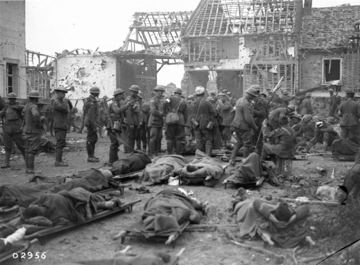 A black-and-white photograph showing a crowded war scene: wounded soldiers are on stretchers while soldiers mill around, with destroyed buildings in the background.