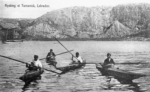 A black-and-white photograph of four men in kayaks with a rocky outcropping in the background.