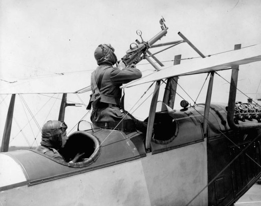 A black-and-white photograph of a biplane with two aviators in the cockpits: one is piloting and the other is at the machine gun.