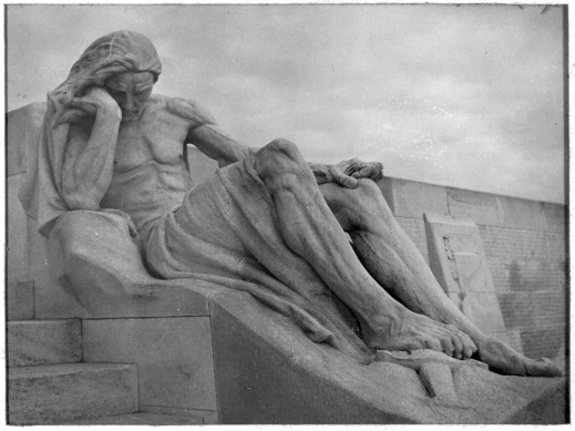 A black-and-white photograph of a dramatic view of a larger-than-life sculpture from the Vimy Memorial, a man in mourning with his foot resting on a sword. In the background are side panels bearing the names of Canadian dead.