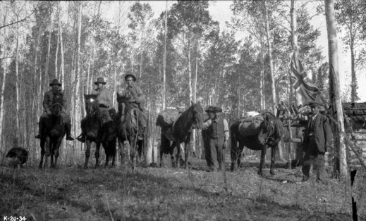 A black-and-white photo of six men. Three men are mounted on horses, and three are unmounted standing next to two horses.