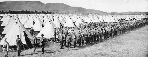 A black-and-white photo showing a field of white tents as far as the eye can see, and a long line of soldiers conducting military exercises in the foreground.