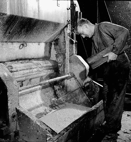 A black-and-white photograph of a man leaning over a grinder machine holding a plank of wood in his hands.