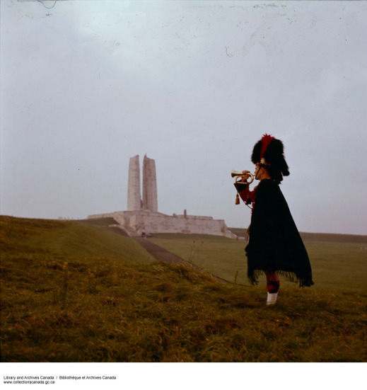 A colour photograph of a bugler in Highland uniform in front of the Vimy Ridge memorial.