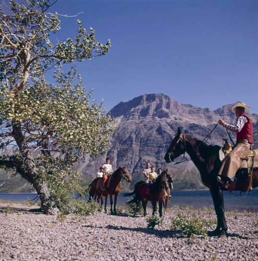 "A colour photograph of a group of people on horseback by a river with a mountain peak in the background. One is dressed in ""cowboy"" attire and appears to be leading a family on a trail."