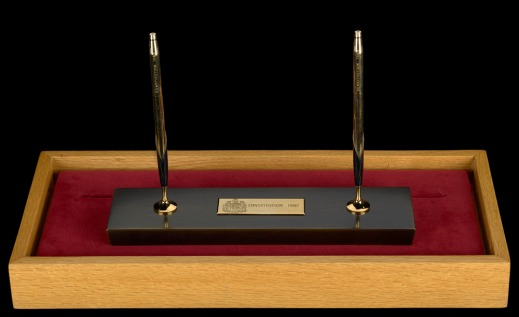Two gold and black pens standing upright in a gold and black pen stand resting on a velvet pad in a wooden box.