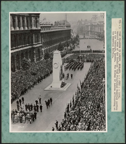 A black-and-white photograph of a large crowd lined on the sidewalk of street while a cenotaph ceremony is taking place in the centre with soldiers in formation in front of a large white cenotaph.