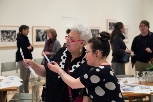 A colour photograph of two Inuit women looking closely at a picture. The older one holds the picture while the younger one takes a photo on her iPhone of it. Behind them are people talking and tables covered with papers.