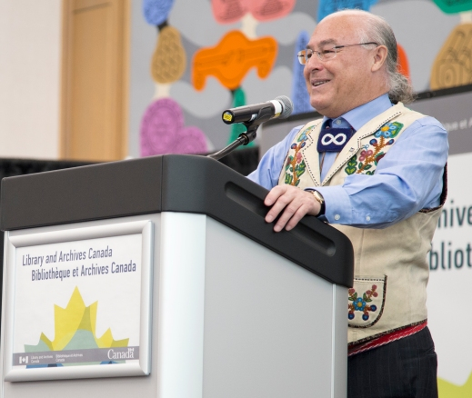 A colour photograph of a man from the Métis Nation wearing a beaded vest standing at a podium.