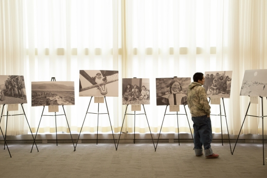 A colour photograph of a young Inuit man looking at several large photographs on easels.