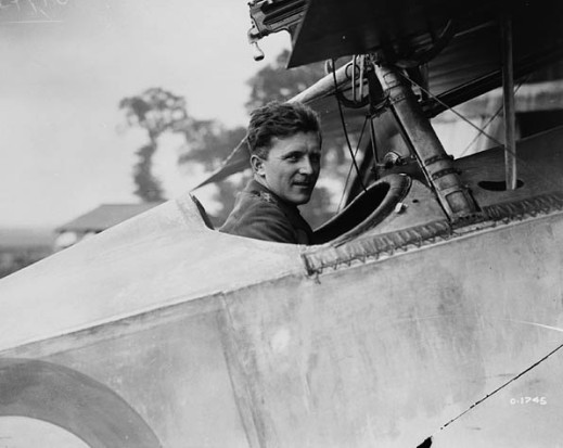 A black-and-white photograph of a man sitting in the open cockpit of an airplane looking at the viewer.