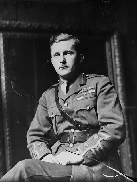 A black-and-white photograph of a military officer seated with his hands in his lap. He is wearing the characteristic Sam Browne belt, which is a wide leather belt with a narrower strap that passes diagonally across the body over the right shoulder.