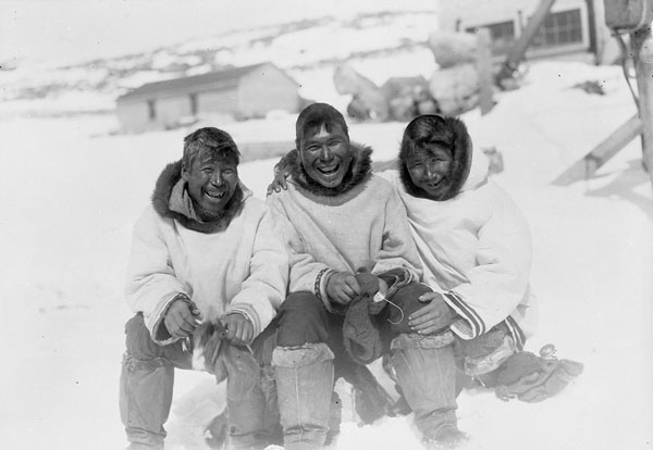 Black and white photograph of three men sitting outside in a row wearing parkas and smiling.