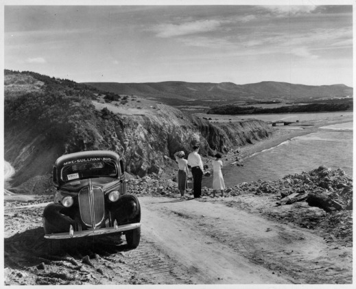 Black and white photo of two women and a man standing on the edge of a dirt road near the coast looking at the ocean