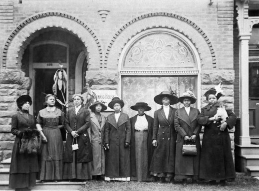 Black and white photograph of nine women wearing dresses, coats and hats standing in front of a residential building.