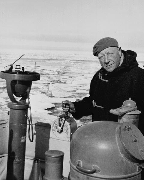 A black-and-white photograph of a man dressed in winter clothing aboard a boat with icy water in the background.