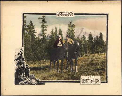 A colourized image showing a man and woman on horseback in a clearing before tall green trees and snow-capped mountains. The man is wearing a yellow shirt unbuttoned to expose his chest. He is reaching over to the woman who is wearing a white cap and red cloak. At the bottom left is a second image, a black-and-white cut-out of a uniformed officer leading his horse to a campfire with a tall tree in the background. The movie title is on the right side of the poster.
