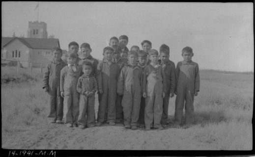 Group of Inuit children dressed in overalls or coveralls standing on sandy, grassy ground with the school in the background.