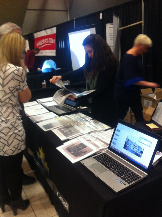 Photograph of a booth covered in photos with a computer on the side. A brown-haired woman staffing the booth is finding a photo for a couple visiting the booth. Another booth is in the background.