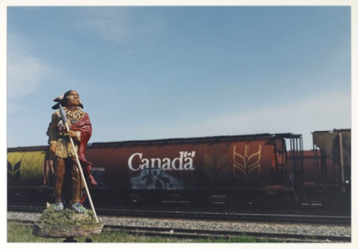 "First Nations figure set in front of a train marked ""Canada"" with grain graffiti on its side."