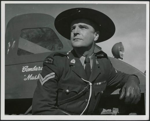 Black-and-white still of an actor in an RCMP uniform leaning against a Bombardier truck.
