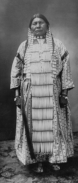 A black-and-white photo of a Dakota First Nation woman wearing a striped dress under a long beaded breastplate. It is matched with a necklace, long earrings and braids.