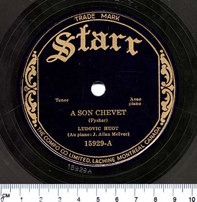 "A colour photograph of a black circular label at the centre of a 78-rpm disc. Gold lettering reads: ""Starr, Tenor, Avec piano, A SON CHEVET (Fyscher), LUDOVIC HUOT (Au piano: J. Allan McIver). 15929-A"""