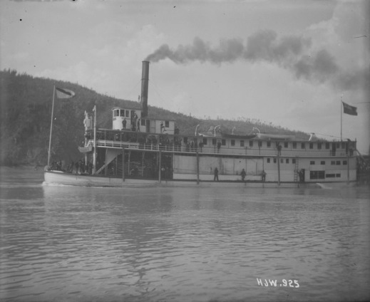 A black-and-white photograph of the port side of a passenger steamer. People are gathered at the bow and on the second level deck.