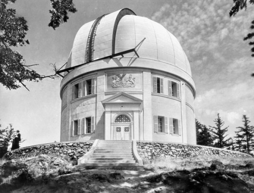 A black-and-white photograph of a cylindrical building, with an observatory cupola, on top of a hill.
