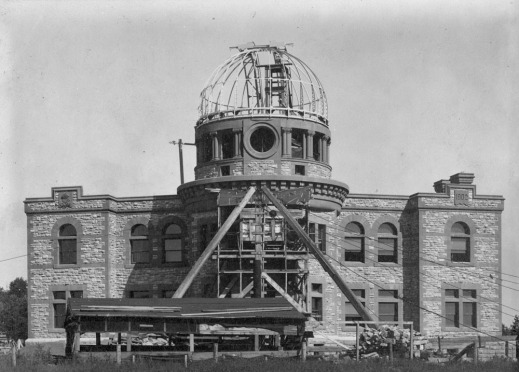 View of a building under construction. The building's construction is almost complete, but there is scaffolding in front of the building, and the metal structure of the cupola is still under construction.
