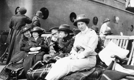 A black-and-white photograph of a group of four women sitting on deck chairs with blankets. Three of the sisters are wearing the dark overcoat while one is wearing a lighter coloured jacket. A soldier can be seen slightly in the middle of the group.