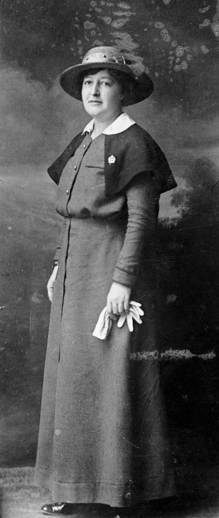 A black and white photograph of a woman in a nursing sister uniform with the cape, pin, hat and white gloves.