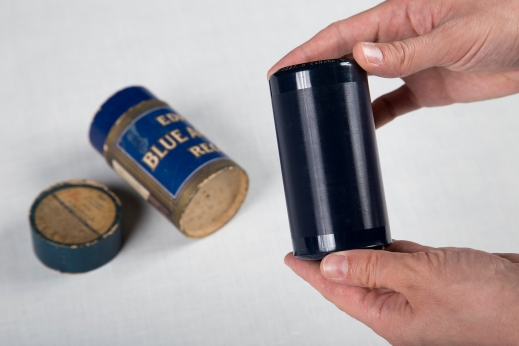 A colour photograph of hands holding a dark blue grooved cylinder. In the background is the cardboard case for the cylinder.