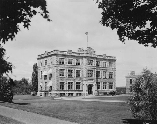 A black-and-white photograph of a 3-storey, stone, and mortar building located on a large grassy area.