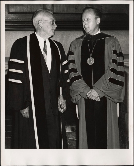 A black-and-white photograph of two men standing side by side in doctoral gowns.