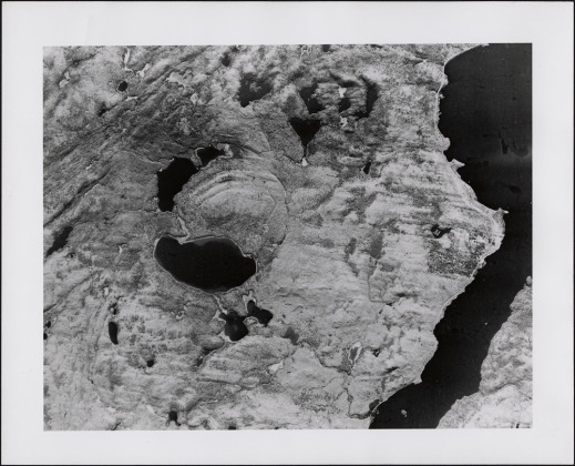 A black-and-white aerial photograph of a crater. The arc of a circle is visible in an area now consisting of lakes and hills.