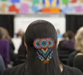 Colour photograph of a multi-coloured, beaded hair clip decorating the back of a woman's head. The woman is sitting in the Pellan Room of Library and Archives Canada, listening to a panel of speakers.