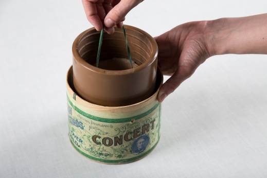 "A colour photograph of a wax cylinder being pulled out of its protective cardboard container by a string that is attached on the inside of the cylinder. On the cardboard, the word ""Concert"" appears in uppercase letters, while above, in smaller print, can be read ""National Phonograph Co, New York, U.S.A."" ""Made at the Edison Laboratory, Orange, N.J."" is visible below."