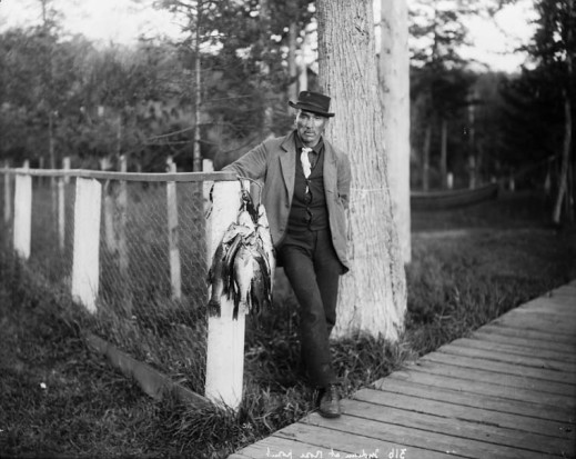 A black-and-white photograph of a man wearing a hat, coat and tie leaning against a fence post and holding a string of fish.