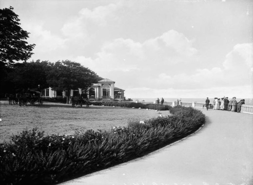 A black-and-white photograph of an elegant path with a stone fence on one side leading to a small building. Horses rest under the trees.